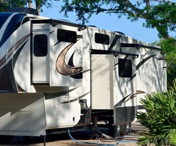 Image of white fifth wheel connected to campground utilities