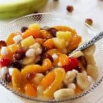 Square image of colorful canned fruit salad recipe in a bowl with peaches, grapes, pineapple, cherries, banana, and marshmallows.