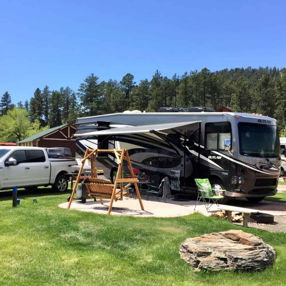 Feature image of a class A motorhome and the surrounding campsite that has been set up with a firepit, table, chairs, grill, rug, and other items.