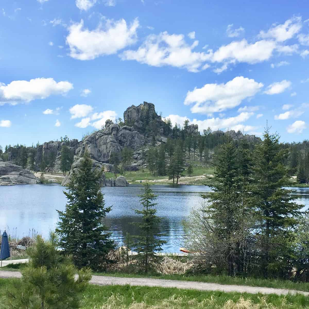 Square feature image of Custer State Park Lake Sylvan. Craggy rocky outcrops overlook a beautiful lake.