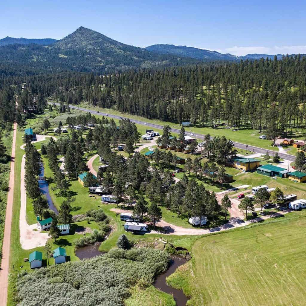 Aerial view of Crooked Creek RV Resort Black hills SD, featuring a view of the hills in the background and a creek running through the RV park. Very wooded and scenic park