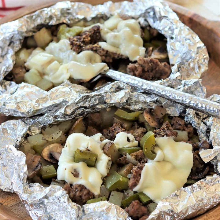 Feature image with a closeup of Philly Cheese Steaks Foil Packets cooked and ready to eat with melted cheese.