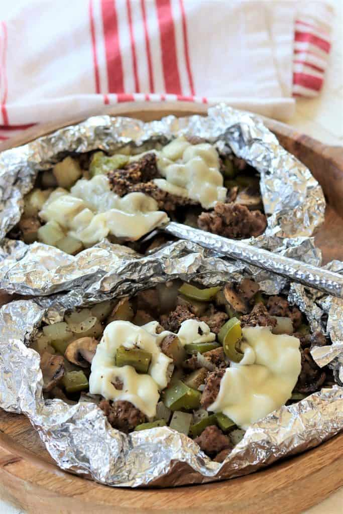 Portrait image of two cooked philly cheese steak foil packets opened and ready to eat with melted cheese.