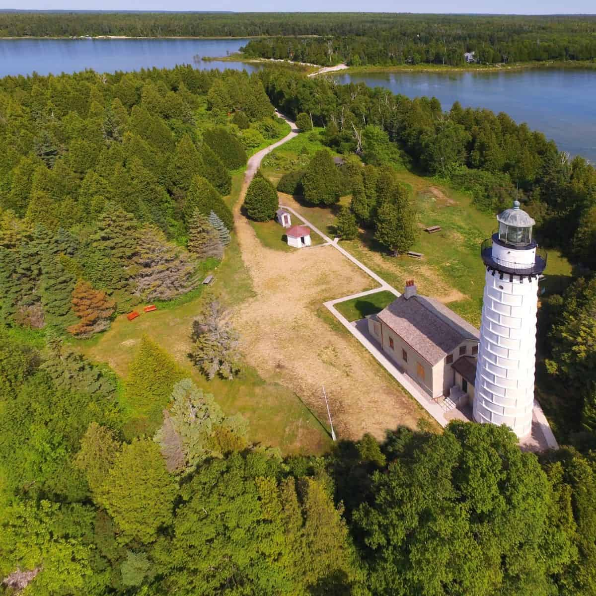An aerial view of Canna Island Lighthouse with inland door county in the background.