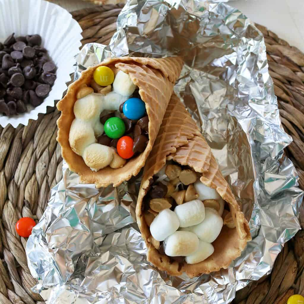 Feature image of campfire cones on foil with melted marshmallows, chocolate, M&M's, and peanut butter chips.
