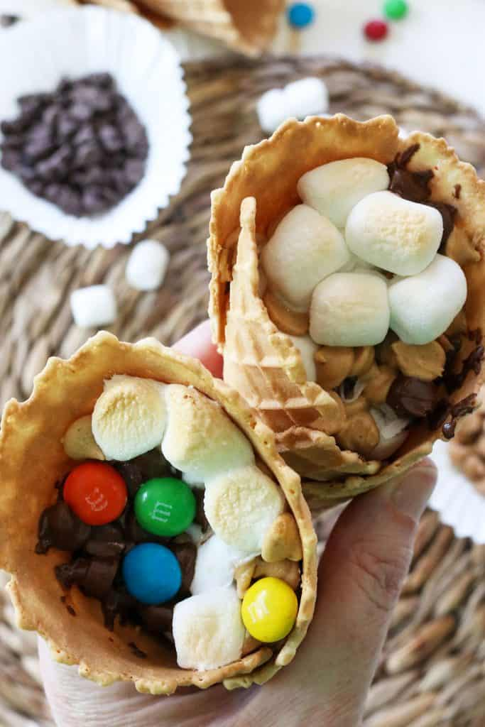 Portrait image of campfire cones with melted marshmallows, chocolate, M&M's, and peanut butter chips.